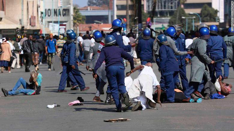 Riot police clash with demonstrators protesting a ban on an opposition rally in Harare on Friday.